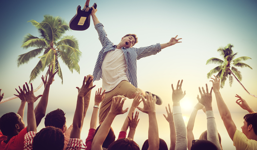 man jumping into excited crowd holding a guitar and cheering